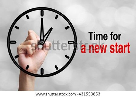 Hand is drawing a clock with text Time For a New Start Concept aside with blurred gray background. - stock photo