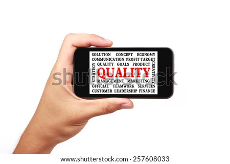 Hand is holding a smart phone with the quality word cloud isolated on white. - stock photo