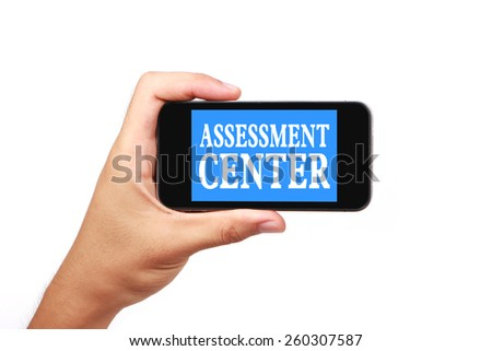 Hand is holding a smart phone with the text Assessment center isolated on white. - stock photo