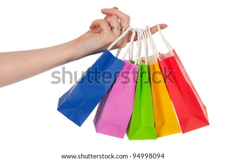 Hand is holding many colorful shopping bags - stock photo