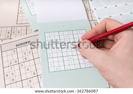 Hand is holding pencil and is solving sudoku crossword with numbers. - stock photo