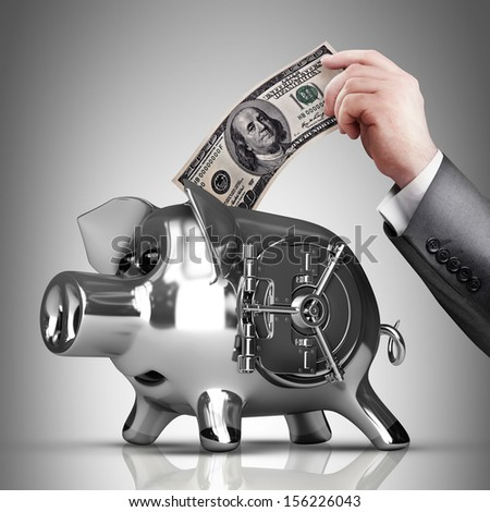 Hand is putting money into piggy bank. High resolution  - stock photo