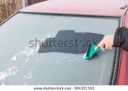 Hand is scraping ice from the windshield of the red car using an ice scraper in the early morning light. - stock photo