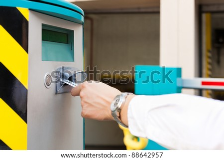 Hand is slipping parking ticket into barrier of the parking garage, close-up - stock photo