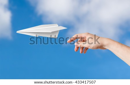 Hand is throwing origami paper airplane. Blue sky on background. - stock photo