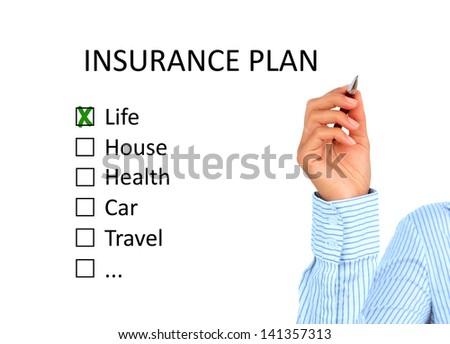 Hand is writing insurance plan. - stock photo