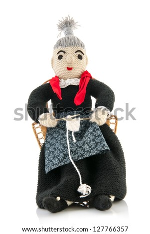 hand knitted grandma sitting on chair and knitting - stock photo