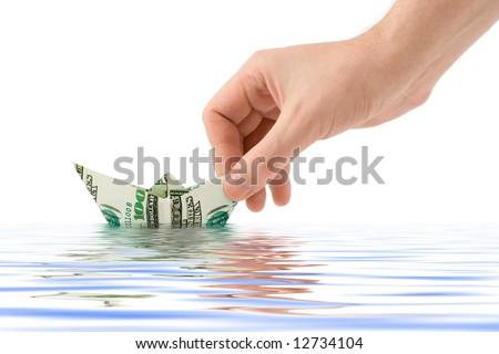 Hand launching money ship, isolated on white background - stock photo