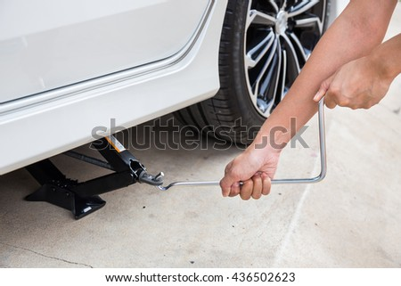 Hand lifting a car with spanner jack-screw - stock photo