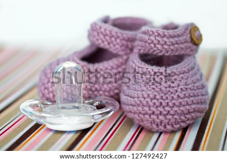Hand-made baby shoes and a pacifier - stock photo