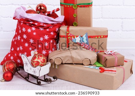 Hand-made Christmas gifts and Christmas bag with balls on floor in room - stock photo