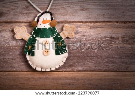 Hand made felt snowman Christmas decoration. Vintage style, over old wood background, with space for your text. - stock photo