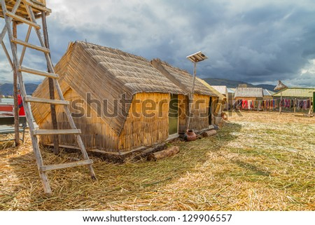 Hand made houses in Uros with solar panels, artificial islands made of floating reeds, Peru, South America. - stock photo