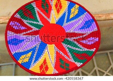 Hand made many colored basketry underplate for injera food with ethiopian decorative patterns. Handicraft shop in Mek'ele-Mekelle town at 2084 ms.high in Debubawi-Southern zone. Tigray region-Ethiopia - stock photo