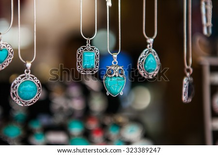 Hand made oval pendants with turquoise stone in a silver frame on market - stock photo