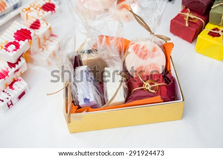 Hand made soap on white cloth, custom paper packaging. Trade show table with gift ideas and packaged in a box. - stock photo