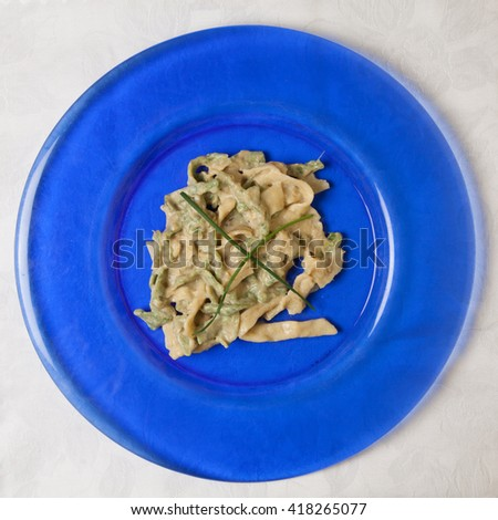 "Hand made ""Straw and hay"" tagliatelle pasta with artichoke cream and chive garnish. On blue glass plate with white background - stock photo"