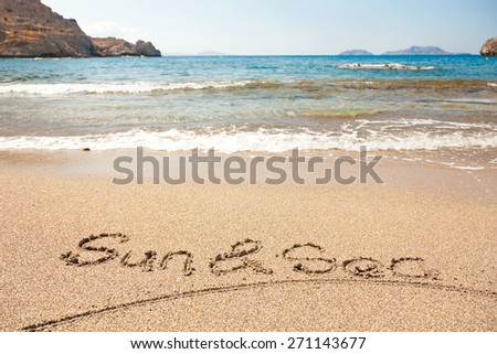 Hand made text in sand on a beach - Sun and Sea - stock photo