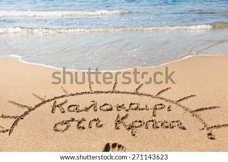 """Hand made text in sand on a beach  which translates from Greek as """"Summer in Crete"""" - stock photo"""