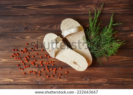 Hand-made wooden slippers for sauna, Russian baths or spa with red mountain ash or rowan berries on rustic wooden background - stock photo