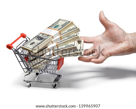 hand magnetize shopping cart full of stacks of dollar bills isolated on white  - stock photo