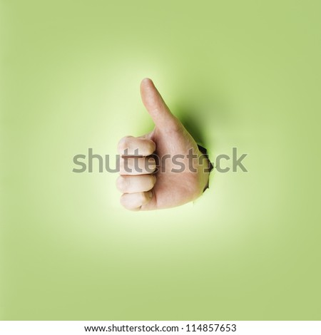 Hand making a thumb up gesture through a hole in green paper. - stock photo