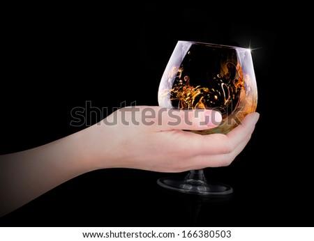 hand making toast with glass splashing Cognac or brandy on black background - stock photo