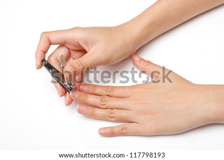 hand manicure with nail clipper on white background - stock photo
