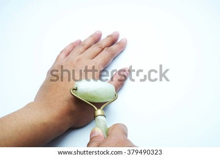 Hand massage with jade roller. Isolated on white background. - stock photo