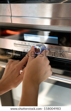 Hand moving the timer knob on the  oven - stock photo