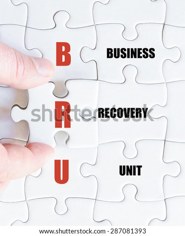 Hand of a business man completing the puzzle with the last missing piece.Concept image of Business Acronym BRU as Business Recovery Unit - stock photo