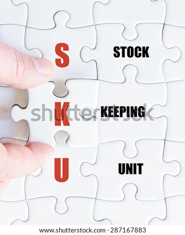 Hand of a business man completing the puzzle with the last missing piece.Concept image of Business Acronym SKU as Stock Keeping Unit - stock photo