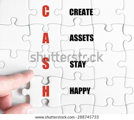 Hand of a business man completing the puzzle with the last missing piece.Concept image of Business Acronym CASH as Create Assets Stay Happy - stock photo