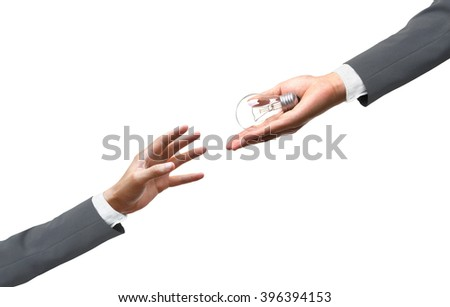 hand of a businessman giving a light bulb to other businessman - stock photo