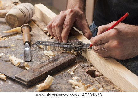 hand of a carpenter taking measurement of a wooden plank - stock photo