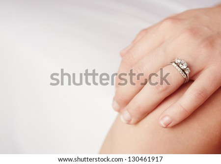 Hand of a caucasian adult woman with a diamond engagement ring on her left ring finger - stock photo