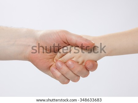 Hand of a child in the hand of her father, closeup shot - stock photo