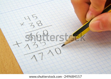 Hand of a child making a multiplication with a pencil. Math. School concept - stock photo