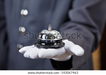 Hand of a concierge with a hotel bell - stock photo