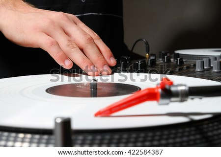Hand of a DJ playing music on turntable with white vinyl record in dark studio or nightclub. High class analog sound equipment for concert or party - stock photo