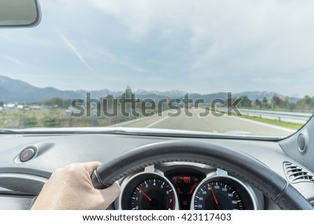 Hand of a driver on the steering wheel on a highway on a partly cloudy day with the alp in the far background - stock photo