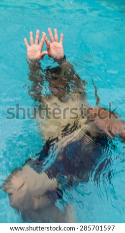 hand of a drowning person stretching out of the water in a swimming pool(Motion blur) - stock photo