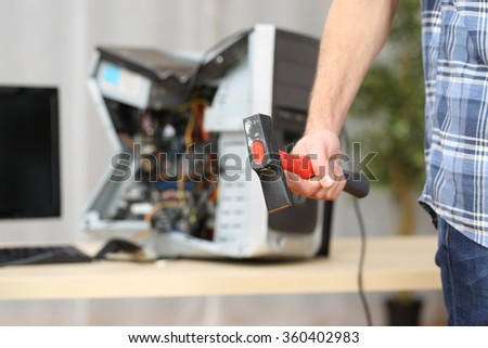 Hand of a furious hot-tempered man holding a hammer after destroying a computer on a table - stock photo