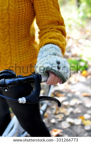 Hand of a girl in a knit glove holding a bicycle steer - stock photo