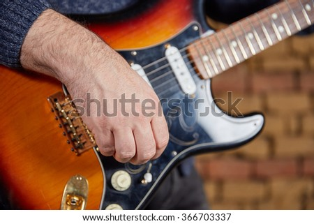 Hand of a guitar player turning the knobs of an electric guitar with bricks in the background - stock photo