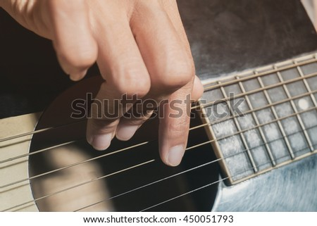 Hand of a  guitarist playing acoustic guitar - stock photo