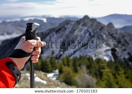 Hand of a man holding a hiking pole on top of a mountain - stock photo