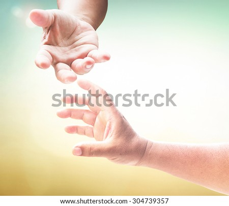 Hand of a man reaching to hand of GOD, or hand holding puzzle over blurred beautiful sunrise or sunset background. Thanksgiving Christmas Forgiveness Mercy Repentance Evangelical Humanitarian concept - stock photo