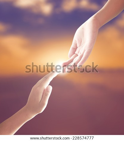 Hand of a man reaching to hand of GOD over blurred sunset. - stock photo