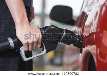 Hand of a man refueling a car - stock photo